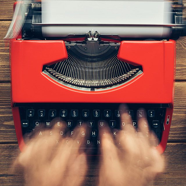 Hands typing on a red typewriter